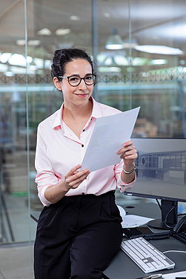 Smiling businesswoman with strategy sitting at desk in office - p300m2265189 by Florian Küttler