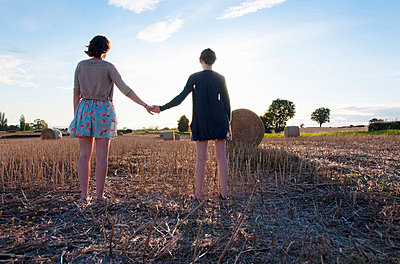 Girls holding hands in hay field - p42916831f by Simon Potter