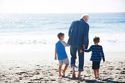 Grandfather with two grandsons, walking on beach, rear view - p924m1125786f by David Jakle