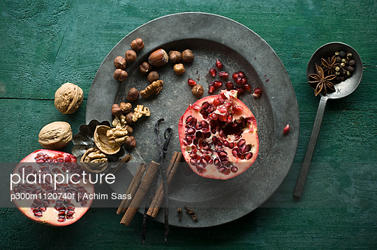 Two halves of pomegranate, different spices and nuts on tin plate - p300m1120740f by Achim Sass