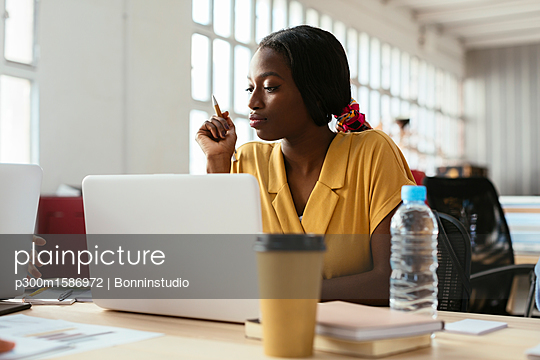Young woman using laptop at desk in office - p300m1586972 von Bonninstudio