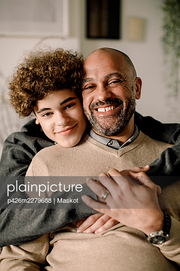 Portrait of smiling boy hugging father - p426m2279688 by Maskot