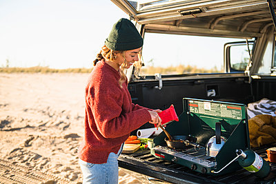 Young woman tailgate cooking while beach car camping alone - p1166m2285571 by Cavan Images