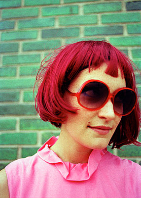 A woman with bright pink hair, pink shirt, and red sunglasses - p3010478f by fStop