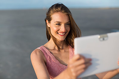 Young woman on beach using tablet computer - p341m1480704 by Mikesch