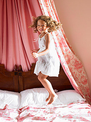 Girl jumping on a bed - p4296177 by Ghislain & Marie David de Lossy