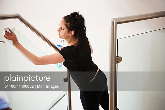 Woman standing on a staircase, cleaning a glass pane and banister rail. - p1100m1490052 by Mint Images