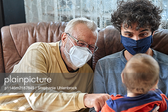 Grandfather with face mask, son and grandson in the livingroom - p1146m2187845 by Stephanie Uhlenbrock
