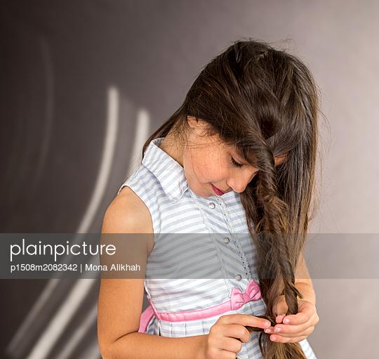 Mädchen spielt mit ihrem langen Haar - p1508m2082342 von Mona Alikhah