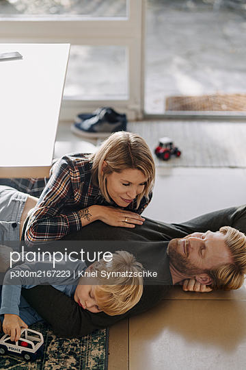 Happy relaxed family lying on the floor together at home - p300m2167223 by Kniel Synnatzschke