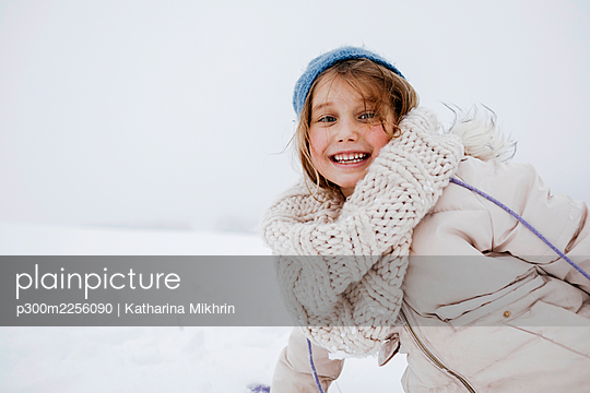 Playful girl smiling in warm clothing during winter - p300m2256090 by Katharina Mikhrin