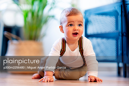Cute baby boy playing while sitting on floor at home - p300m2256480 by Miguel Angel Partido Garcia