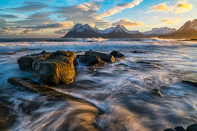 Sunset over the mountains of the Strandir Coast, Iceland as the surf pounds the shoreline; West Fjords, Iceland - p442m2004279 by Robert Postma