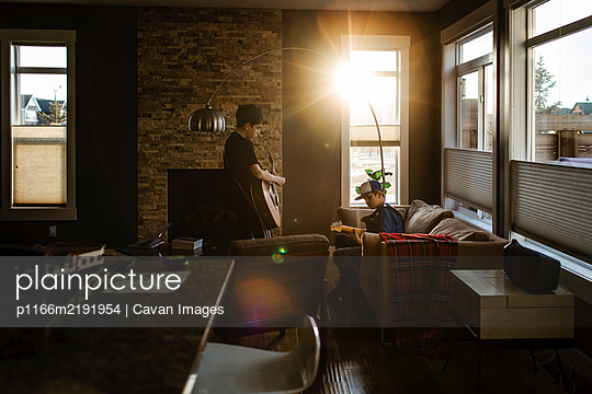 Brothers playing guitar at home with sun coming in window - p1166m2191954 by Cavan Images