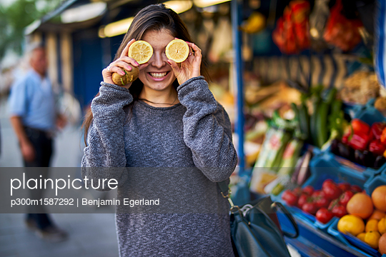 Laughing young woman on market covering her eyes with lemon halves - p300m1587292 von Benjamin Egerland