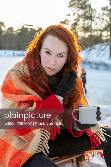 Beautiful woman holding coffee mug during winter - p300m2287657 by Frank van Delft
