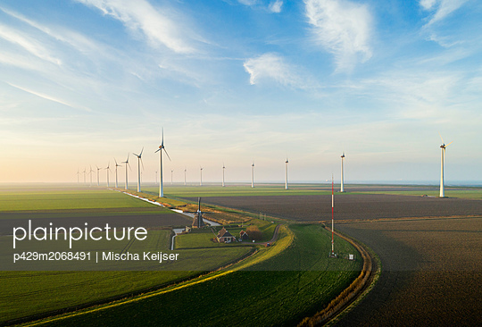 Wind turbines with traditional windmill in foreground, Eemshaven harbour, Groningen, Netherlands - p429m2068491 by Mischa Keijser