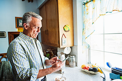 Senior man standing in a kitchen, using a mobile phone. - p1100m1177500 by Mint Images