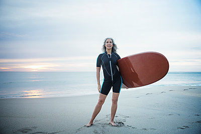 Full length portrait of confident female surfer carrying surfboard at Delray Beach - p1166m1141441 by Cavan Images