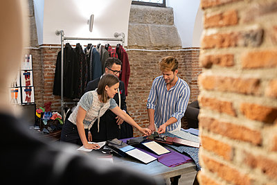 Man choosing fabrics with tailor and assistant - p1166m2261436 by Cavan Images