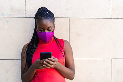 woman with African braids sending a message from her smartphone - p1166m2269218 by Cavan Images