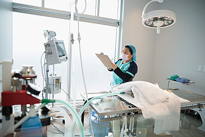 Veterinarian with clipboard checking monitor in operating room - p1192m1127934f by Hero Images