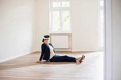 Woman in empty apartment wearing VR glasses - p300m1460191 by Uwe Umstätter