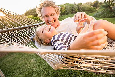 Happy father and son lying in hammock together - p300m2167536 by Floco Images