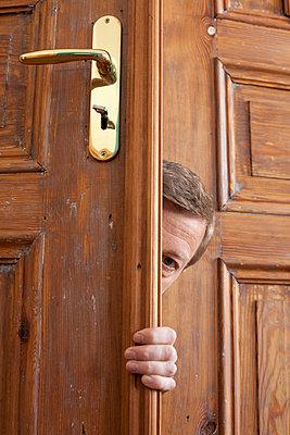 Man hiding behind a door - p3041025 by R. Wolf