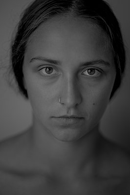 Portrait of young woman with nose piercing - p552m2248546 by Leander Hopf