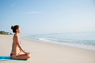 Caucasian woman meditating on beach - p555m1420643 by JGI/Jamie Grill