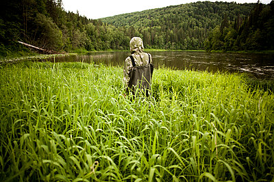 Mari man in wading boots standing in tall marsh grass - p555m1420947 by Aliyev Alexei Sergeevich