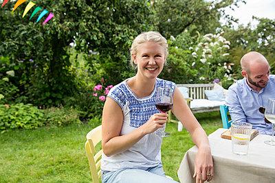 Junge Frau trinkt Rotwein auf einer Gartenparty - p788m1165389 von Lisa Krechting