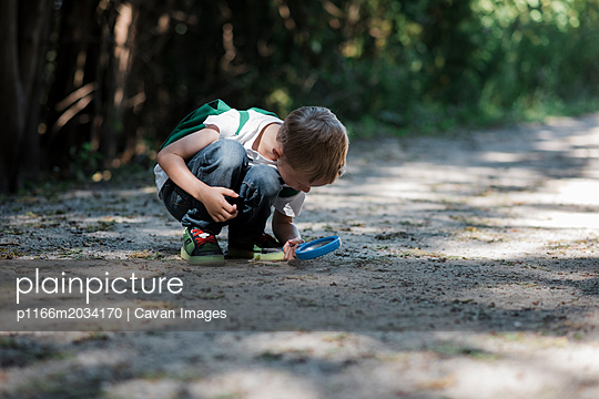 Boy looking on field through binoculars in forest - p1166m2034170 by Cavan Images
