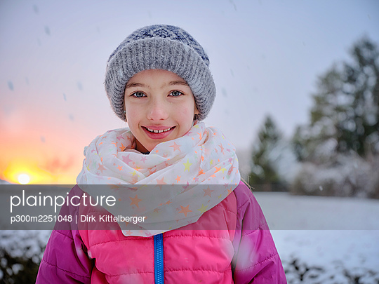 Cute smiling girl in warm clothing during sunset in winter - p300m2251048 by Dirk Kittelberger