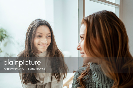 Smiling girl looking at mother through window at home - p300m2257155 by Rafa Cortés