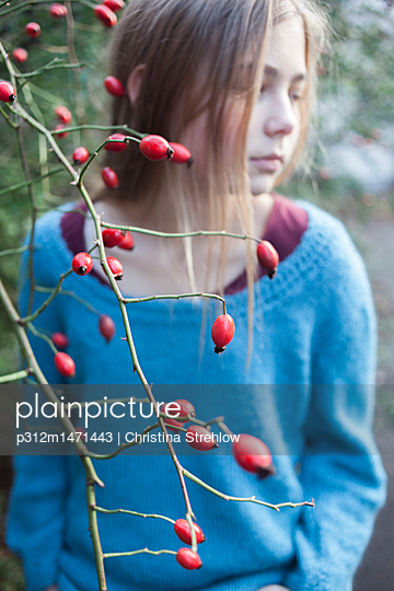 Twigs with berries, girl on background - p312m1471443 by Christina Strehlow