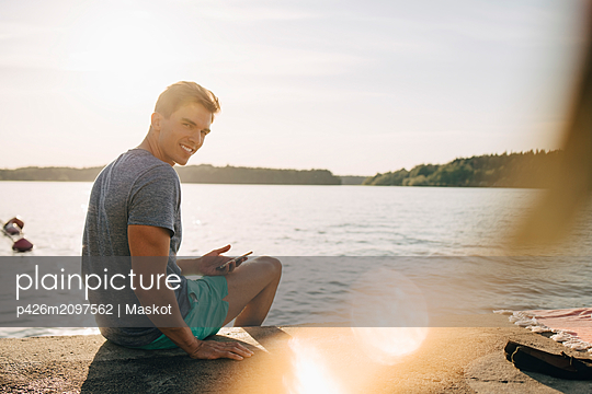 Portrait of smiling young man sitting with mobile phone on jetty by lake - p426m2097562 by Maskot