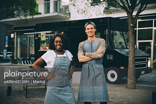 Portrait of smiling male and female owners standing against food truck in city - p426m2213261 by Maskot