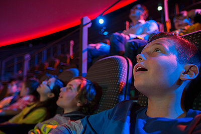 Surprised students enjoying planetarium show - p1192m1019867f by Hero Images