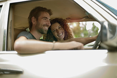 Happy young couple in car traveling during road trip - p300m2290457 by LOUIS CHRISTIAN