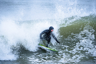 Surfer riding wave in sea - p343m1585193 by Cate Brown