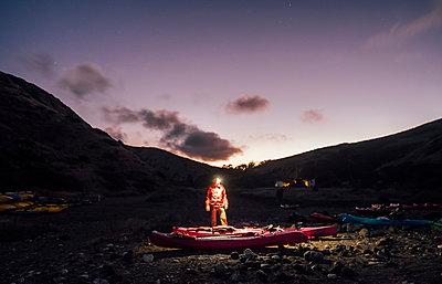 Young man in headlamp preparing sea kayaks at night, Santa Cruz Island, California, USA - p924m1506727 by JFCreatives