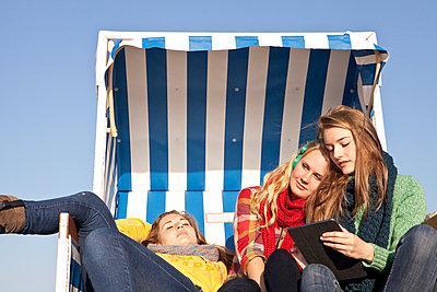 Three girls in a hooded beach chair - p981m952214 by Franke + Mans