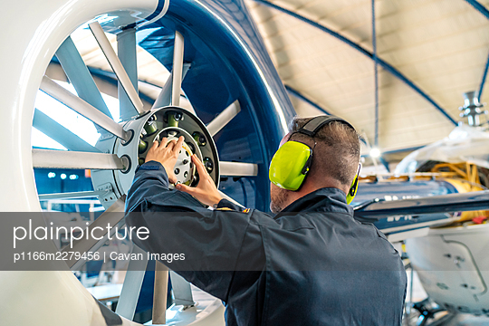 professional mechanic repairing helicopter engine - p1166m2279456 by Cavan Images
