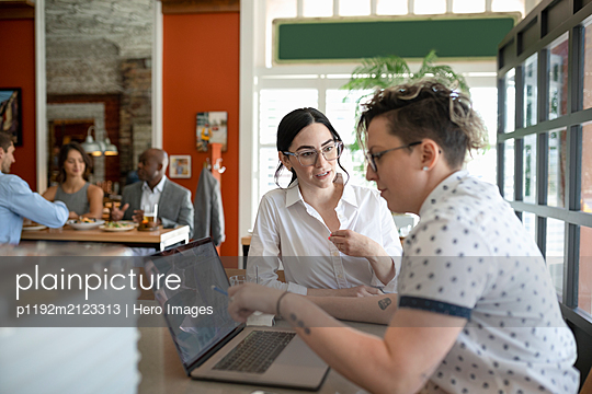 Business owner using laptop talking to staff in restaurant - p1192m2123313 by Hero Images