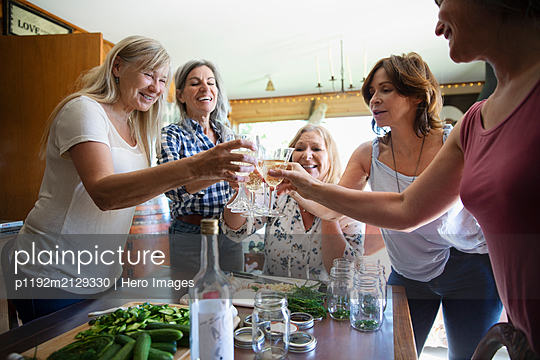 Group of friends toasting wine at kitchen table - p1192m2129330 by Hero Images