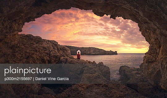 Rear view of man sitting on cave at sunset, Menorca, Spain - p300m2155697 by Daniel Vine Garcia