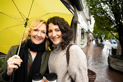 Portrait smiling women friends with coffee under yellow umbrella - p1192m1583374 by Hero Images