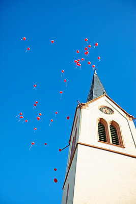 Red ballons next to steeple - p1312m1333156 by Axel Killian